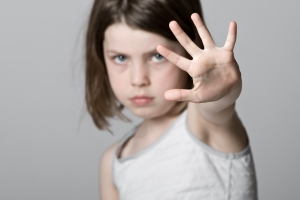 a child holding up her left hand toward the viewer