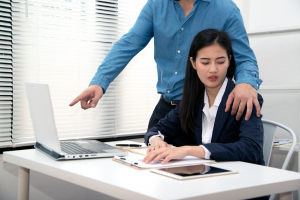 a male coworker placing his hand on a female coworker's shoulder