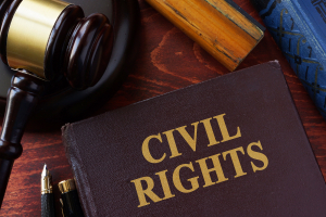 a book that reads Civil Rights sitting next to a gavel on a wooden surface